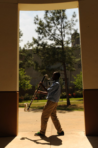 photo of a bass clarinetist practicing outside the music building